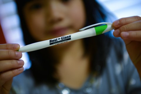 A student holding Best in Class pen with the contact information
