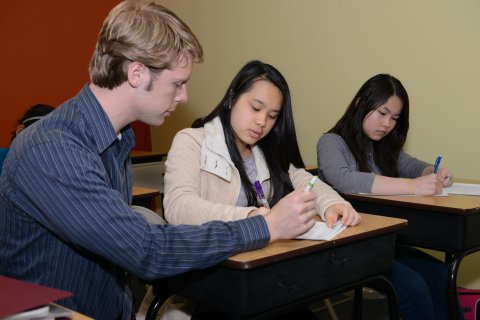 An instructor helping a students in the classroom with packet
