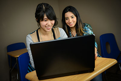 Two women working together on a laptop computer