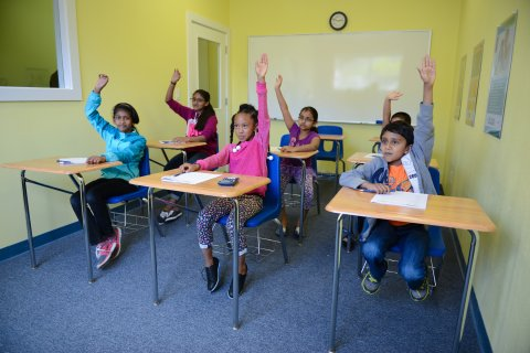 A group of Students sitting in the classroom with hands up