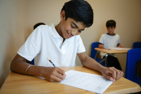 A student smiles while working on a homework packet.