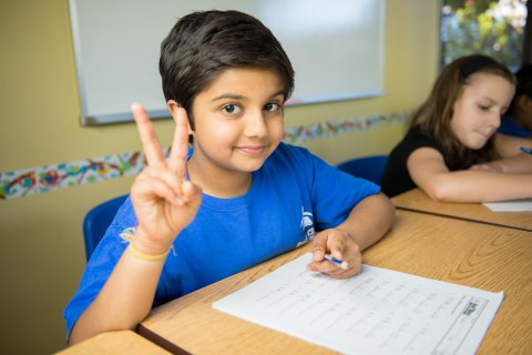 A student working on a packet, gives the camera a peace sign.