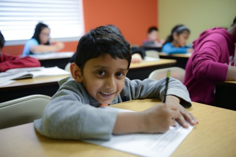A student smiles at the camera while working on a packet.