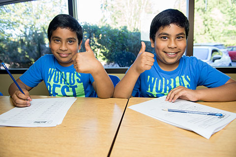 Two students sit at their desks and give the camera smiles and thumbs up.