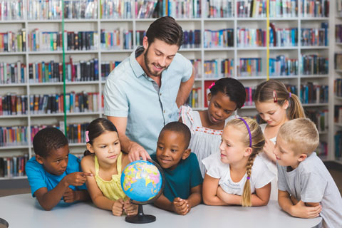 Teacher points at globe while group of children observe